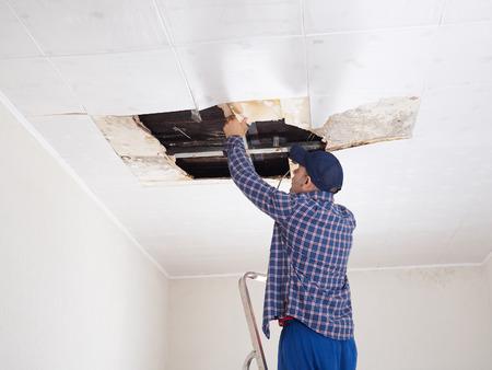 Man repareren ingestort plafond. Stockfoto
