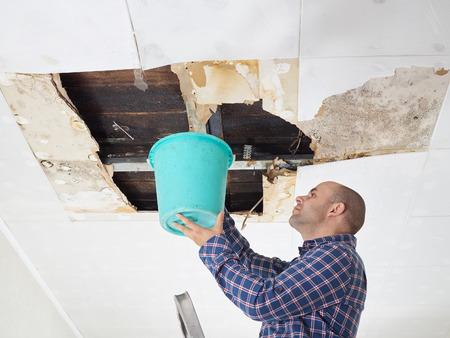 天井からバケツで水を集める男。天井パネルが破損しています。