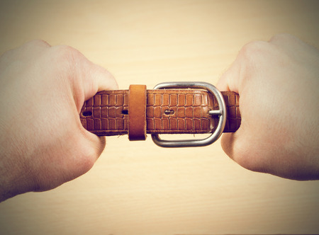 Two hands pulling a leather belt in opposite directions isolated on wood background