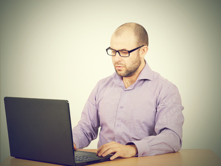busy beard: Busy man with beard in glasses thinking over laptop with  on the table. Isolated on white background