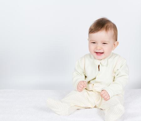 Petit bébé drôle de garçon en costume assis. Sur blanc. Banque d'images