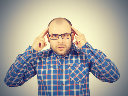 neurosis: Man with glasses holding his head with his hands. Stress, neurosis, disorder .Isolated on a gray background. Stock Photo