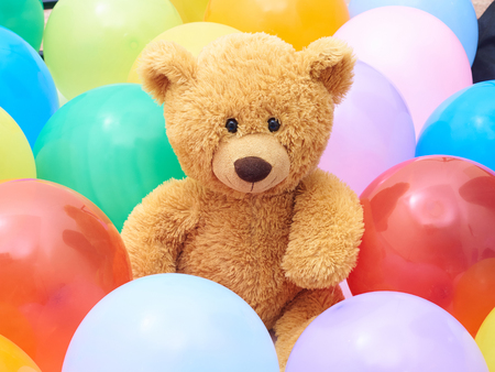 balloons teddy bear: Teddy bear  in colourful balloons closeup.Background of many colorful balloons.