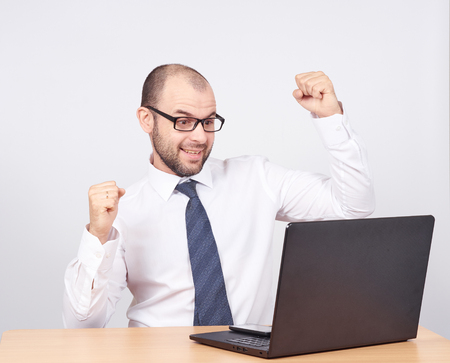 exult: Funny photo of businessman bald with beard wearing shirt and glasses.  angry businessman working with laptop at table. Isolated on white background Stock Photo