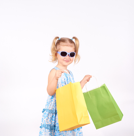playing the market: Shopping child. little girl holding shopping bags. Isolated on white background