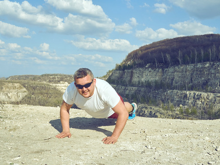 man doing pushups outdoors in nature. An active holiday. Fitness, sports. Lifestyle.