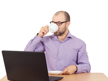 busy beard: Busy man with beard in glasses thinking over laptop with  on the table. With a Cup of coffee.Isolated on white background Stock Photo