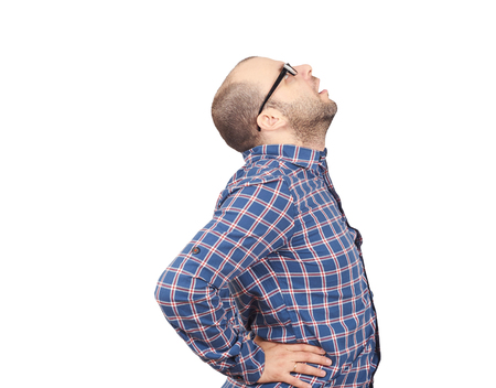 struggles: Caucasian man in blue shirt struggles with intense back pain on white background.