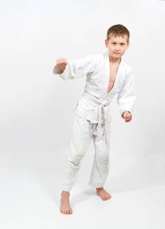 karate boy: Karate boy in white kimono fighting isolated on gray background