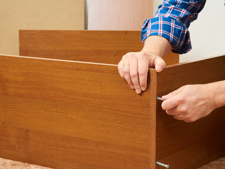 self assembly: Man in shirt assemble furniture. Domestic work. Craftsman. Carpenter. Stock Photo