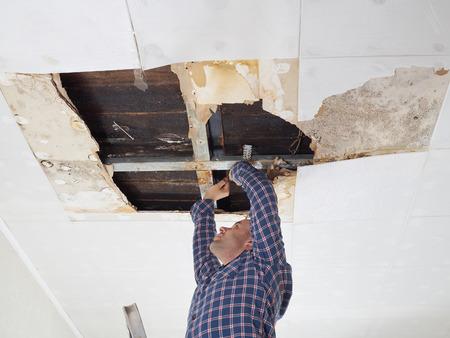 Mens die ingestort plafond herstellen. Plafondpanelen hebben een enorm gat in het dak van regenwaterlekken beschadigd. Water beschadigd plafond. Stockfoto - 55750277