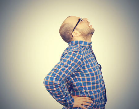 throb: Caucasian man in blue shirt struggles with intense back pain on gray background.