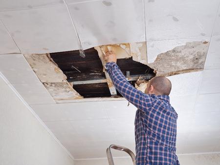El hombre la reparación se derrumbó el techo. Los paneles de techo dañados enorme agujero en el techo del agua de lluvia leakage.Water dañado techo.