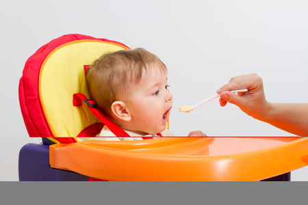 highchair: Baby boy eating with spoon at home in highchair