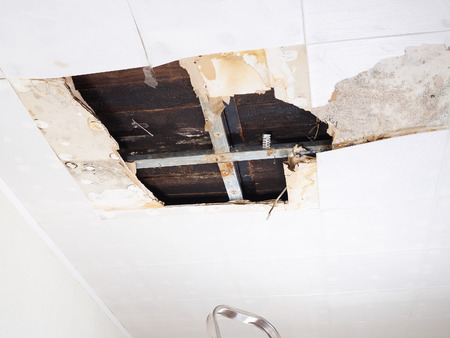Ceiling panels damaged  huge hole in roof from rainwater leakage.Water damaged ceiling . Stock Photo