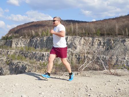 hacer footing: Hombre gordo que se ejecuta en vacaciones activas nature.An. Aptitud, deportes. Estilo de vida. Foto de archivo