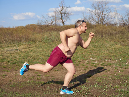 morbidity: Fat man running outdoors on nature.An active holiday. Fitness, sports. Lifestyle. Stock Photo
