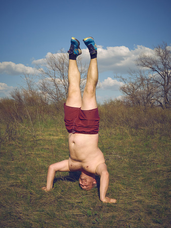 headstand: Fat man doing yoga outdoors in nature. Stock Photo