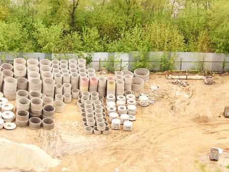 sump: stacks of concrete rings for sewer. of stock vertically stacked concrete drainage pipes, construction site, view from above, Stock Photo