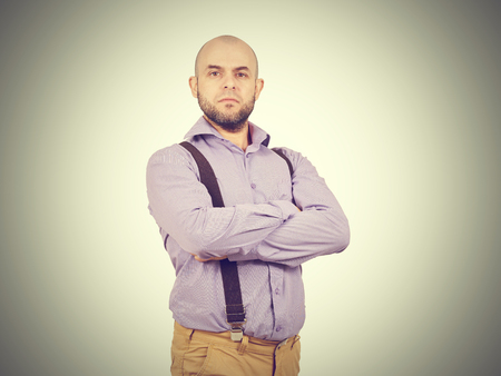 arrogant: Arrogant man businessman in a shirt with suspenders. Bald with a beard. Stock Photo