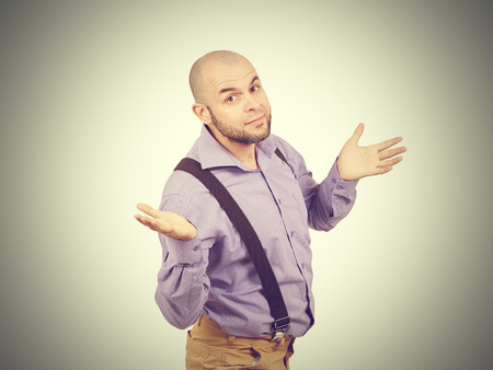 unsettled: Bald bearded man throws up his hands in disbelief. Stock Photo