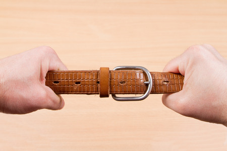 constrict: Two hands pulling a leather belt in opposite directions isolated on wood background