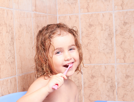 kinky: Little girl brushing her teeth in bathroom Stock Photo
