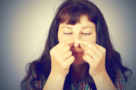zit: beautiful young woman squeezing pimples on her nose