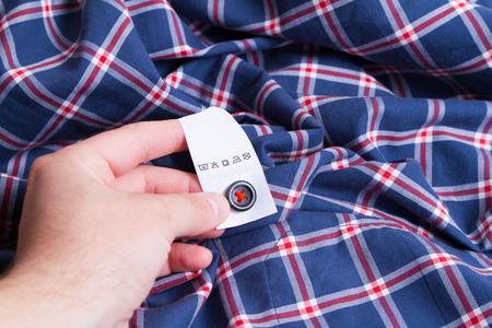 warm things: washing, clothes, housework  - close up of male hands holding shirt and label with instructions Stock Photo