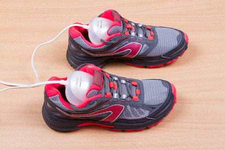 electric dryer: Electric ultraviolet shoe dryer and Sneakers. isolated on wooden background.