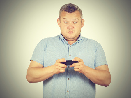insulted: fat man looks at the phone. Playing on a smartphone. Bad news. Emotions.