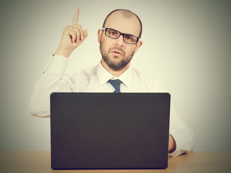 newness: Portrait of businessman pointing finger up, showing something, having an idea.Isolated on  gray background