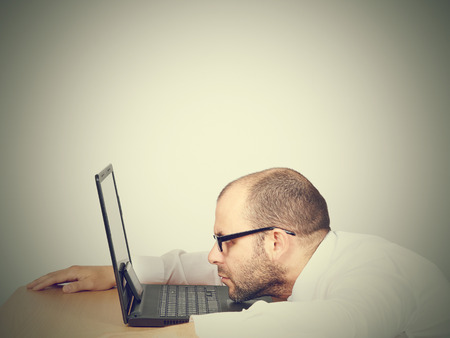 whacked: Tired businessman looking in a computer. Isolated on  gray background