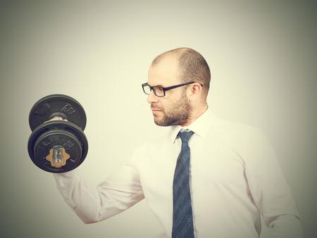 raises: Man Trained businessman raises dumbbell. Isolated on  gray background