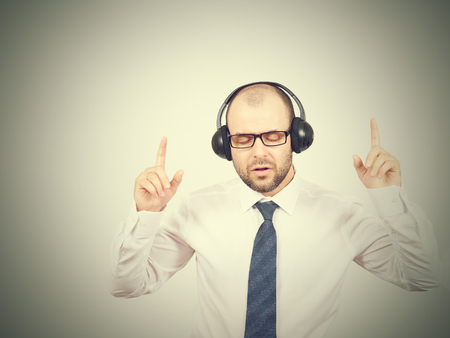 sings: Men in headphones listens to music and sings. Isolated on a  gray background. Stock Photo