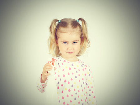 trigger: Little girl holding a watering spray bottle. sprayer trigger Stock Photo