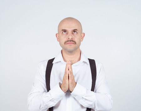 imploring: Bald man praying,imploring, hands clasped hoping of miracle isolated on background.