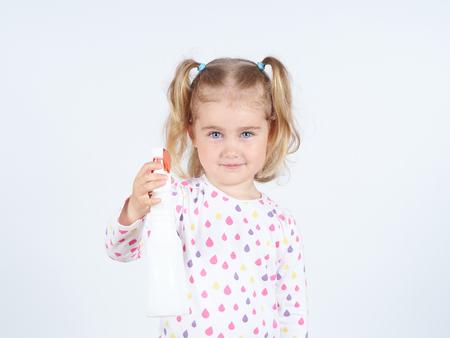 gatillo: Niña que sostiene una botella de spray de riego. el gatillo del pulverizador Foto de archivo