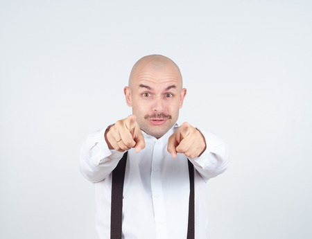 prankster: Haughty bald man with a mustache. It points the finger at the camera.