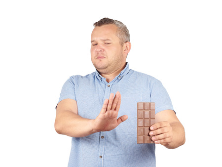 fat food: fat man refuses to chocolate. Diet, overweight, healthy food Isolated on white background.