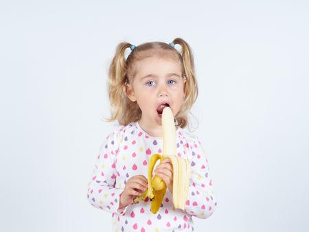frutas divertidas: Niña que come un plátano fresco. Alimentación saludable. Dieta. Vegetarianismo. Foto de archivo