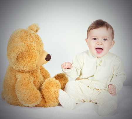 baby sit: Little boy baby sitting next to a teddy bear. On white. Stock Photo