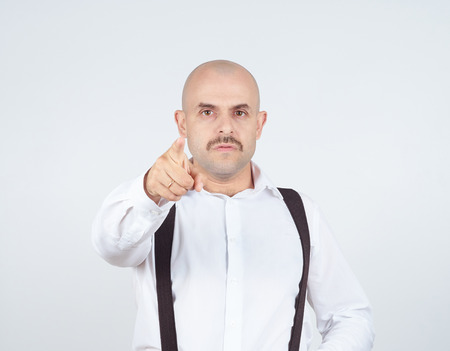 business skeptical: Bald businessman pointing at the camera with. Isolated on background. Stock Photo