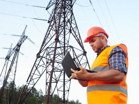 Elektroingenieur arbeiten. Am Telefon sprechen und an einem Laptop arbeiten. Kontrolle der Stromnetze.