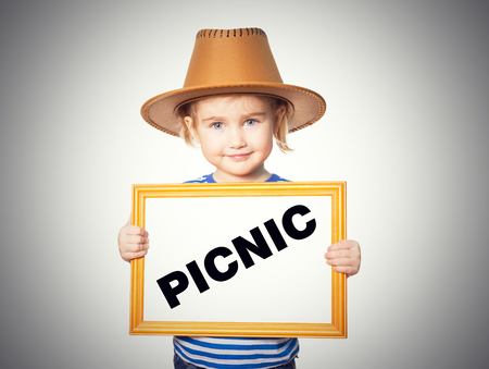 picknick: Little Funny girl in striped shirt with blackboard. Text PICNIC. Isolated on gray background.