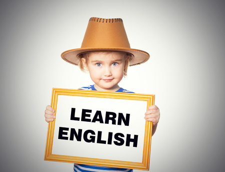 english girl: Little Funny girl in striped shirt with blackboard. Text  learn english.  Isolated on gray background