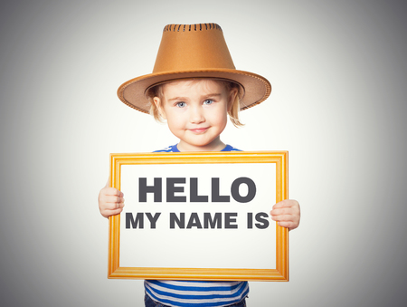 hello my name is: Little Funny girl in striped shirt with blackboard. Text HELLO MY NAME IS.  Isolated on gray background.
