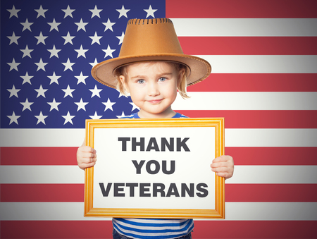 little girl child: Little Funny girl in striped shirt with blackboard. Text THANK YOU VETERANS.On background of  American flag