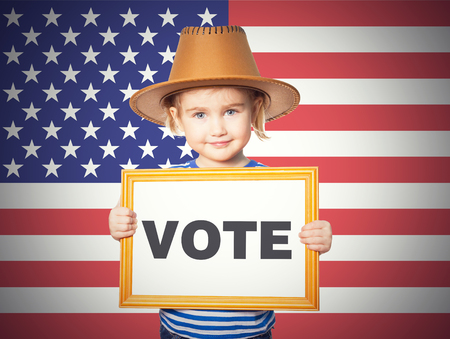 Little Funny girl in striped shirt with blackboard. Text VOTE. On background of American flag. Stockfoto