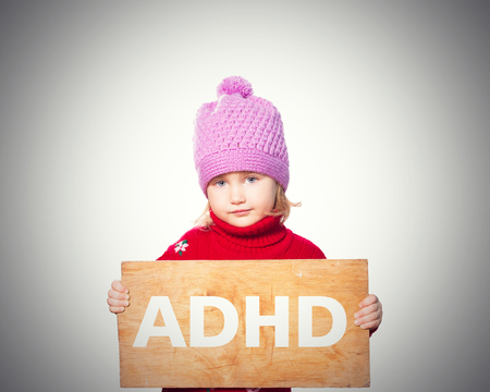 rueful: Little girl holding Board with inscription ADHD. Isolated on gray background Stock Photo